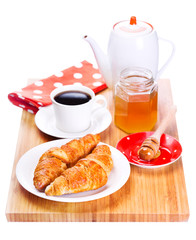 breakfast with croissant, honey and coffee on wooden board