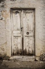 Old white timber door in the scuffed wall