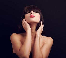 Beautiful glamour woman touching short hair on dark background
