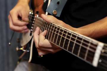 electric guitar close-up with fingers playing it