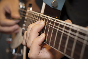 Man with his fingers on the frets of a guitar