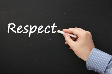 Hand writing the word Respect on a blackboard