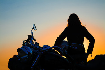 classic motorcycle and girl silhouette at sunset