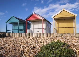 Colorful beach huts on a shingle beach