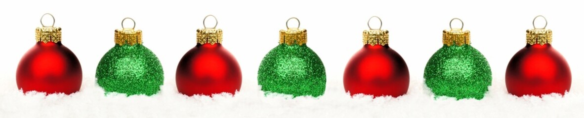 Christmas border of shiny red and green baubles in snow