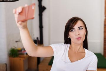glückliche junge frau fotografiert sich mit ihrem handy