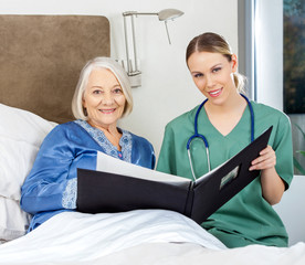 Nurse And Senior Woman With Medical Reports In Bedroom