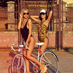 Two sexy women with vintage bike. Outdoor fashion portrait
