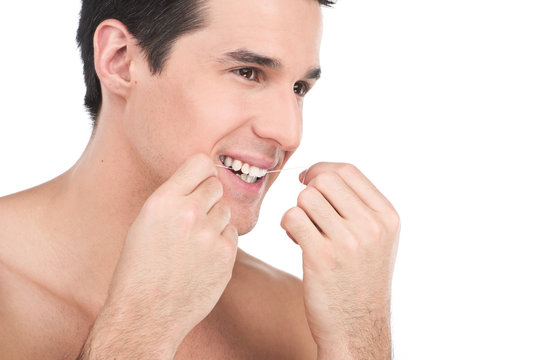 young man flossing his teeth isolated on white background.