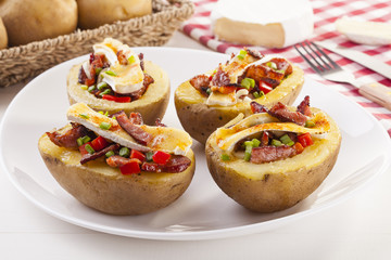 Baked potatoes stuffed with bacon, served with camembert
