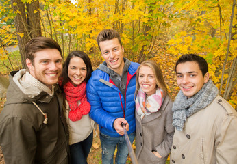 smiling friends taking selfie in autumn park
