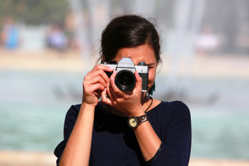 Young woman taking a picture with an old camera