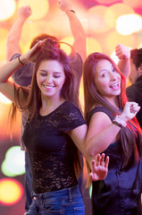 two young girls dancing in a club