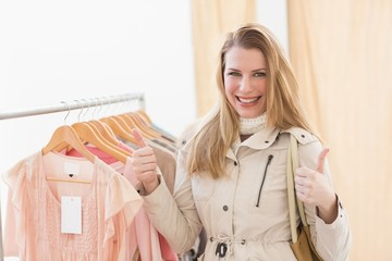 Cute shopping blonde smiling at the camera with thumbs up