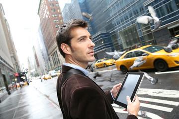 Businessman in Manhattan using digital tablet in the street