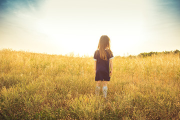 the little girl in costs a back in a field and looks forward