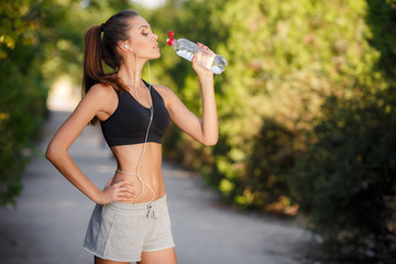 The girl drinks water after jogging