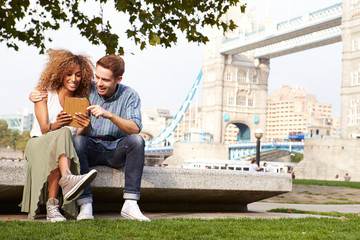 Couple Using Digital Tablet With Tower Bridge In Background