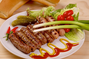 Grilled sausages with vegetables on a white plate