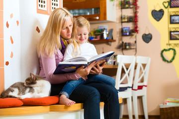 Mutter liest Tochter ein Buch vor in Küche