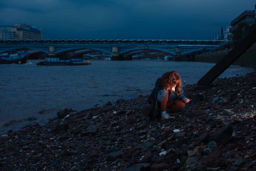 Woman beachcombing in city at night