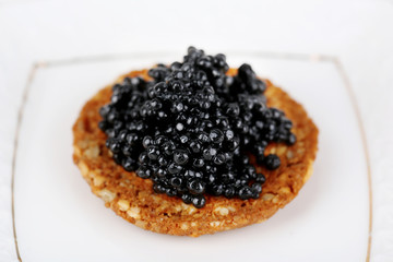Black caviar on crispy bread on plate