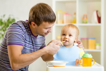 young father teaches his baby son to eat with spoon