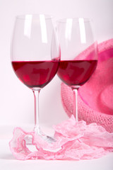 two glasses of red wine on a white background near pink panties