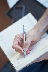 man writes in datebook