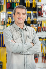 Happy Man Standing Arms Crossed In Hardware Store