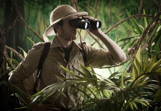 Explorer in the jungle with binoculars
