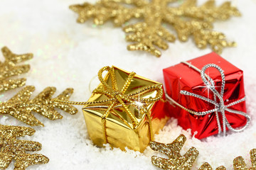 Two Christmas gift boxes with gold snowflakes on snow