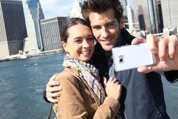 Couple taking picture with Manhattan skyline in background