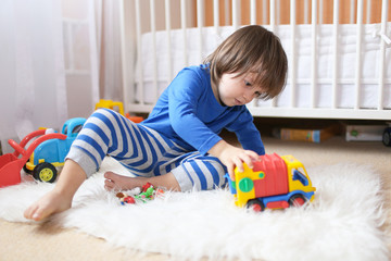 lovely 2 years toddler boy plays cars at home
