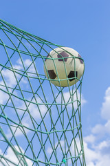 Fototapeta Football caught in goal net with blue sky