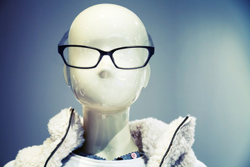 Portrait of white dummy wearing glasses in the clothing store