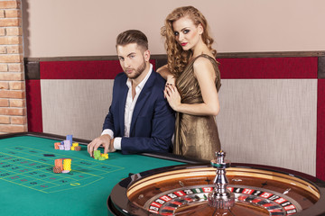 Man and woman by roulette table at casino