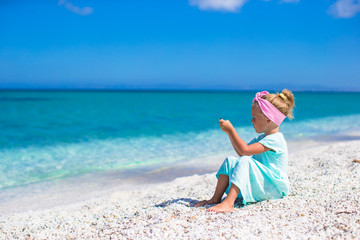 Little adorable girl take picture of the sea on phone at