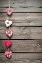 Red hearts hanging over old wood background