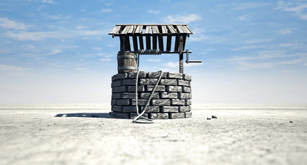 Wishing Well With Wooden Bucket On A Barren Landscape