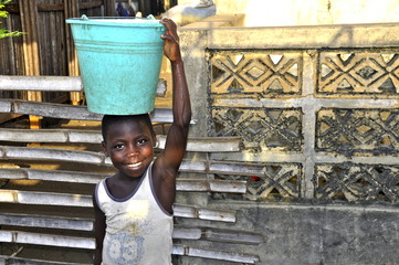 Afrikanisches Mädchen trägt Eimer mit Wasser