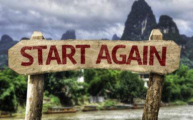 Start Again sign with a forest background