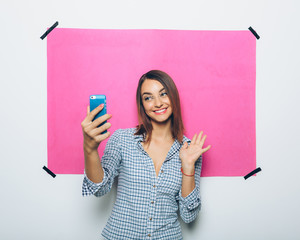 Pretty young woman taking picture with camera phone