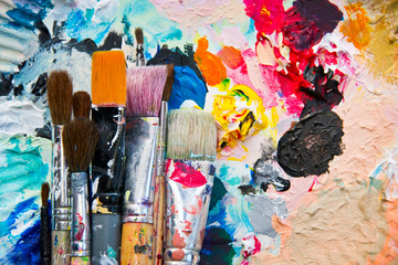 Used paint brushes on a colorful painter palette