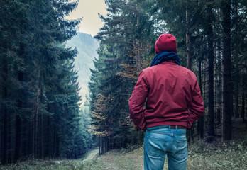 Sad man walking by forest