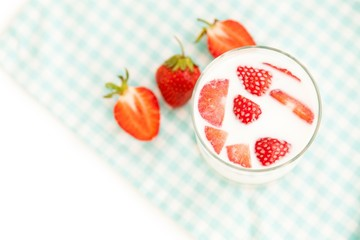 Healthy breakfast: glass of fresh milk and ripe strawberries