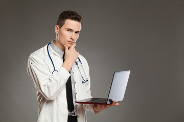 Thinking male doctor with a laptop
