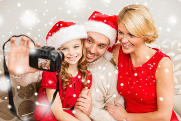 happy family with digital camera taking photo