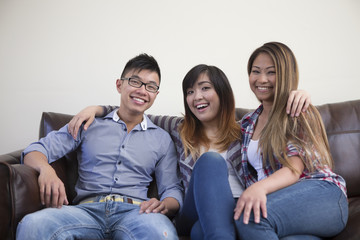 Group of three Asian friends relaxing at home on sofa.