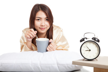 Happy Asian girl  wake up  with alarm clock and  coffee cup